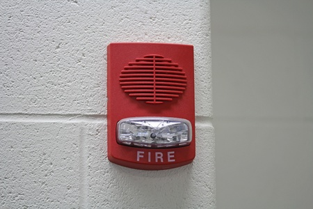 audible: A red fire alarm with built in strobe light to alert in case of fire situated on the corner of a wall with copyspace  Stock Photo