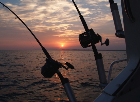 Two fishing poles silhouetted on a boat in front the sun rising on lake Michigan, set up for trolling.