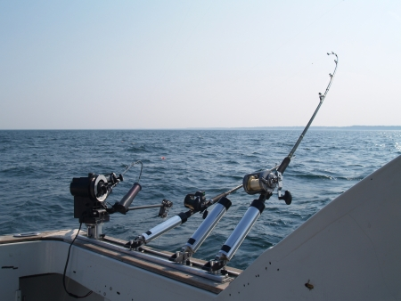 Three fishing poles set up for trolling in lake Michigan on a summer morning with copy space.