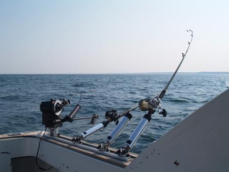 trolling: Tres ca�as de pescar creado para trolling en el lago Michigan en una ma�ana de verano con copia espacio. Foto de archivo