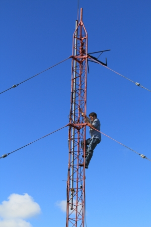 Radio tower or mast, with a worker climbing up it beneath blue sky and copy space.