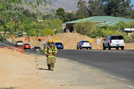 TUCSON, ARIZONA, USA --April 21, 2014   A Firefighter who is training by running alongside the road with his protective suit and air pack on in Arizona