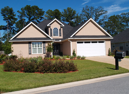 suburban: One story residential low-income home with board or vinyl siding and front entry garage.