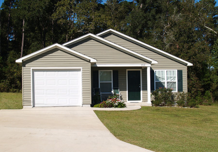 suburb: One story residential low income home with gray vinyl siding and front entry garage.