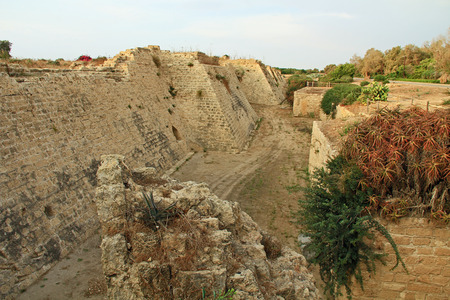 Ruins of fortress and moat in Caesarea Maritima National Park, a city and harbor built by Herod the Great about 25-13 BC. The archaeological ruins are on the Mediterranean coast of Israel and it was the administrative capital. photo