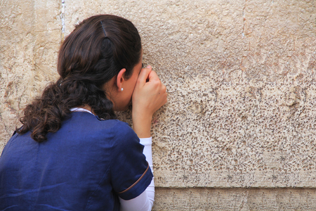 Woman passionately praying at the Western Wailing Wall also known as the Kotel in Jerusalem, Israel.