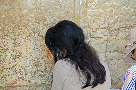 worshipers: Woman passionately praying at the Western Wailing Wall also known as the Kotel in Jerusalem, Israel.