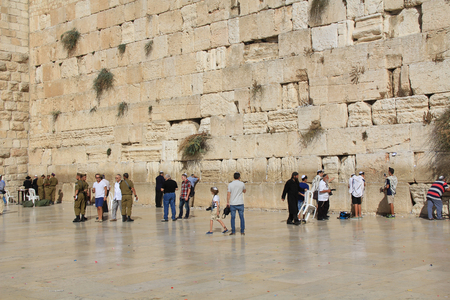 worshipers: JERUSALEM, ISRAEL, OCTOBER 24, 2013, Jewish  soldiers, along with other worshipers praying at the mens side of the Western Wailing Wall which is also known as the Kotel, the most holy site for Jews in Jerusalem, Israel.