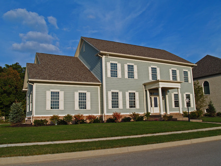 single story: New large two-story gray home styled to look like an historic house.