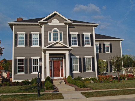New large two-story tan home styled to look like an historic house. Editorial