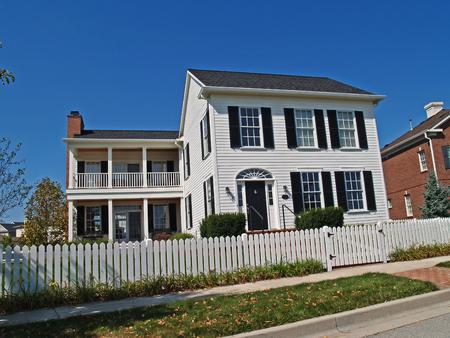 Neues zweistöckiges weißes Haus, das entworfen ist, um wie ein altes historisches Haus mit Zaun im Vorgarten zu sehen.