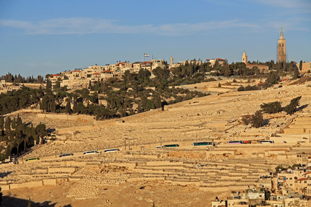 overcrowded: Cemetery and homes on the Mt. of Olives in Jerusalem, Israel.  Tour busses can be seen along the roadside.