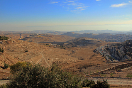 Judean desert wilderness as seen from Mt. Scopus in Jerusalem, Israel with smoky hazy mountains and buildings in the background, Stock Photo