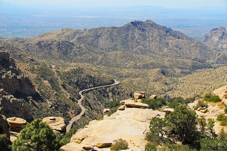 View towards Tucson of winding road from Windy Point on Mount Lemmon in Tucson, Arizona, USA in the Santa Catalina Mountains located in the Coronado National Forest with blue sky copy space.