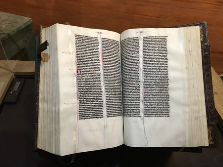 Williamstown, KY, USA - November 3, 2017:  Illuminated Vulgate Pocket Bible from 1250 opened to Romans, demonstrating the long tradition of copying the Bible in Europe in Noahs ark replica at the Ark Encounter Theme Park in Williamstown, Kentucky, USA