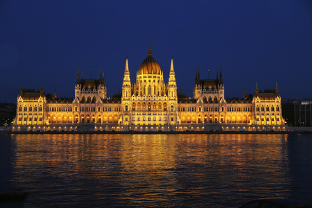 The Hungarian Parliament building on the Danube River in Budapest, Hungary during the night with a dark blue sky copy space.