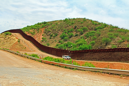 Border Fence beside a road near Nogales, Arizona separating the United States from Mexico with border patrol vehicle.