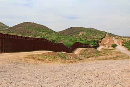 Grenzzaun neben einer Straße in der Nähe von Nogales, Arizona, die die Vereinigten Staaten von Mexiko mit Grenzpatrouillenfahrzeug trennt.