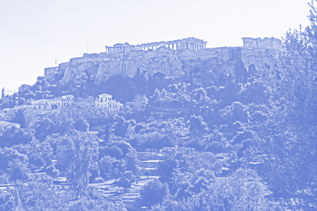 Stylized blue and white image of the Parthenon on the Acropolis in Athens, Greece with a white sky copy space and a beautiful landscape of the neighborhood nearby digitally stylized with digital blue half tone effect.
