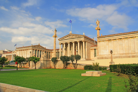 Front view of the National Academy of Arts in Athens, Greece with green lawn and blue sky copy space.