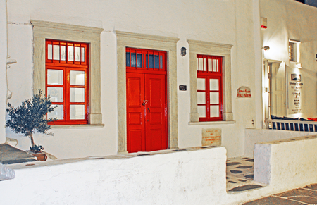 Windows and door on a home in Mykonos, Greece with traditional paint colors of red on white walls with copy space. 版權商用圖片