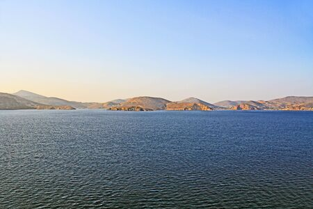 View of the island of Patmos, Greece in the Aegean Sea where St. Paul wrote the book of Revelation in the Bible with beautiful blue sky and water copy space. Stock Photo