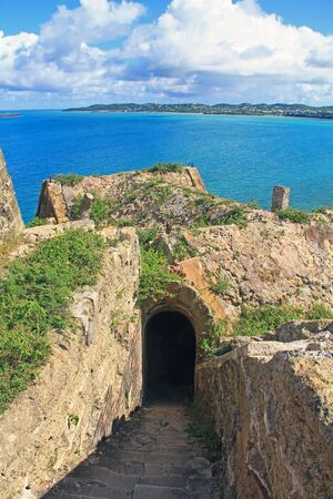 St. John's Bay, stairway looking over roofs of Fort Barrington on Five Islands Peninsula between Deep Bay and St. John's Harbour, Antigua Barbuda Lesser Antilles, West Indies, Caribbean. goat hill.