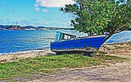 Abandoned blue fishing boat on St. John's Harbor beach in Antigua Barbuda Lesser Antilles, West Indies, Caribbean 版權商用圖片