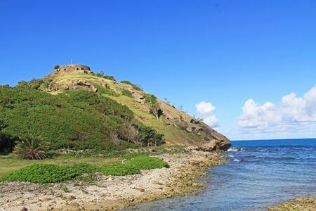 Beach view of Old Fort Barrington on Five Islands Peninsula between Deep Bay and St. John's Harbour, Antigua Barbuda Lesser Antilles, West Indies, Caribbean, Goat Hill with manchineel trees.