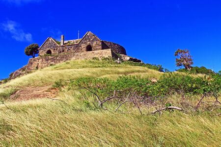 Blue sky copyspace of Old Fort Barrington on the hilltop of Five Islands Peninsula between Deep Bay and St. John's Harbour, Antigua Barbuda Lesser Antilles, West Indies, Caribbean formally known as Goat Hill.