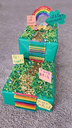 Colorful DIY Leprechaun Trap made by a child and Mom for a school project with, rainbow, ladder, path, signs, path and gold coins. Stock Photo