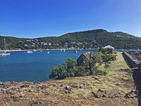 View of English Harbor and boats while walking towards Fort Berkeley peninsula in Antigua and Barbuda, Caribbean, Lesser Antilles, West Indies, with blue sky copy space.