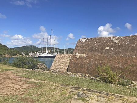 Powder Magazine at Fort Berkeley in Antigua and Barbuda, Caribbean, Lesser Antilles, West Indies with English Harbor in the background and blue sky copy space.