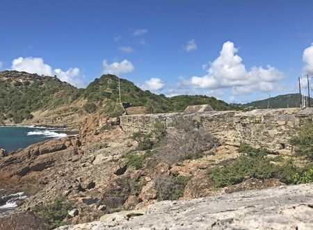 Antigua coastline, outer fort wall and guard house roof as seen from the Fort Berkeley Peninsula in Antigua and Barbuda, Caribbean, Lesser Antilles, West Indies.