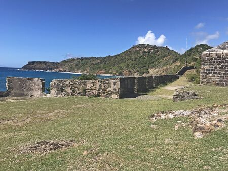 Antigua coastline, Guard House and outer fort wall with cannon ports as seen from the Fort Berkeley Peninsula in Antigua and Barbuda, Caribbean, Lesser Antilles, West Indies with blue sky copy space. 版權商用圖片