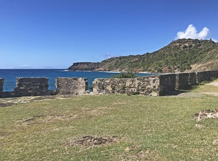 Antigua coastline and outer fort wall with cannon ports as seen from the Fort Berkeley Peninsula in Antigua and Barbuda, Caribbean, Lesser Antilles, West Indies with blue sky copy space. 版權商用圖片