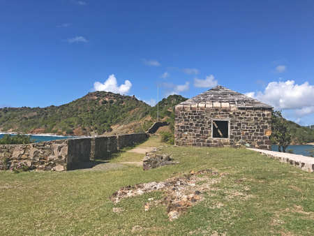 Antigua coastline, Guard House and outer fort wall with cannon ports as seen from the Fort Berkeley Peninsula in Antigua and Barbuda, Caribbean, Lesser Antilles, West Indies with blue sky copy space. 新聞圖片