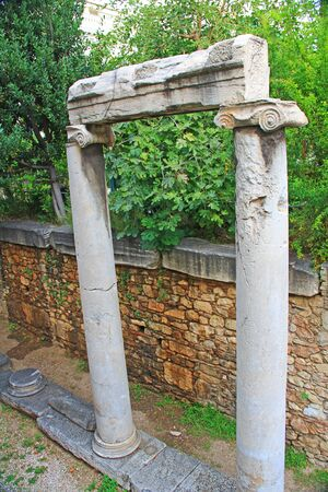 Looking down into an excavated area you will see an old historic marble column doorway located in downtown Athens, Greece.