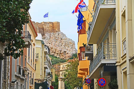 Looking down an Athens, Greece city street lined with homes and a view of the outer wall of Acropolis Hill in the background.
