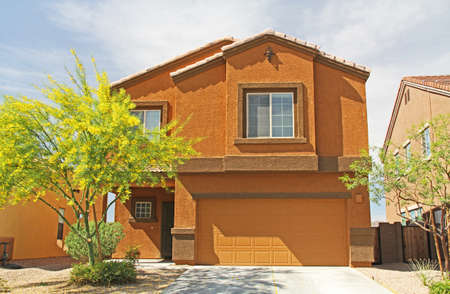 Tucson, Arizona, USA - April 7, 2017:  New two-story, brown and burnt orange stucco home in Tucson, Arizona, USA with beautiful blue sky and landscaping.