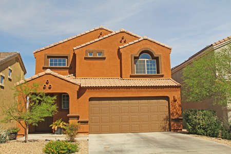 Tucson, Arizona, USA - April 7, 2017:  New two-story, brown and terra cotta orange stucco home in Tucson, Arizona, USA with beautiful blue sky and landscaping.