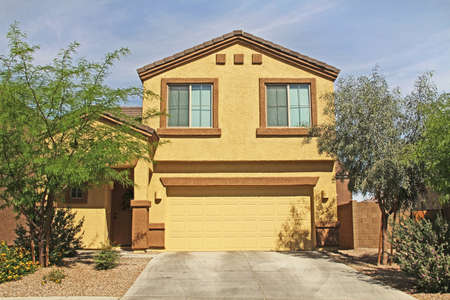 Tucson, Arizona, USA - April 7, 2017:  New two-story, brown and yellow stucco home in Tucson, Arizona, USA with beautiful blue sky and landscaping.