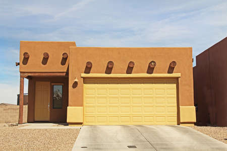 Tucson, Arizona, USA - April 7, 2017:  New ranch, burnt orange terra cotta and yellow, flat roof, stucco home in Tucson, Arizona, USA with beautiful blue sky and landscaping. 新聞圖片