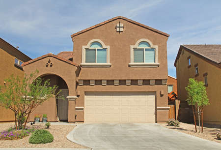 Tucson, Arizona, USA - April 7, 2017:  New two-story, brown and beige stucco home in Tucson, Arizona, USA with beautiful blue sky and landscaping.