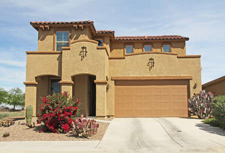 Tucson, Arizona, USA - April 7, 2017:  New two-story, brown and tan beige stucco home in Tucson, Arizona, USA with beautiful blue sky and landscaping.