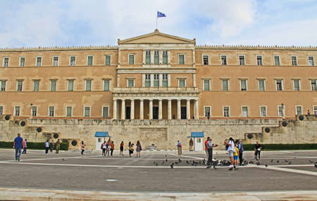 Athens, Attica, Greece – October 18, 2018:  The Greek Parliament and the Tomb of the unknown soldier with tourists and pigeons on the square in Athens, Greece.
