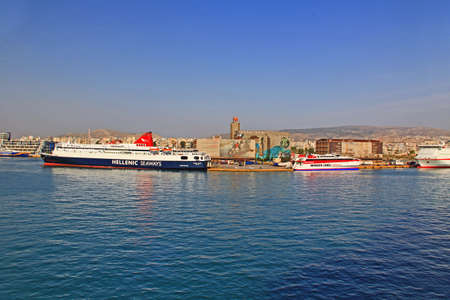 Port of Piraeus, Athens, Attica, Greece – October 18, 2018:  Port Piraeus with ferry boats and view of city and mountains in the background and blue sky copy space.