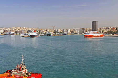 Port of Piraeus, Athens, Attica, Greece – October 18, 2018:  Port Piraeus with ferry boats, freighters, tug boat and cruise ships with view of city and mountains in the background and blue-sky copy sp 新聞圖片