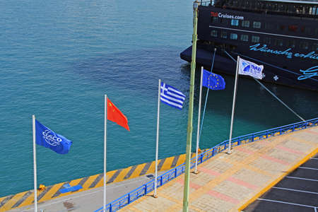 Port of Piraeus, Athens, Attica, Greece – October 18, 2018:  Five flags flying on the dock in the harbor of Piraeus, Athens, Greece.
