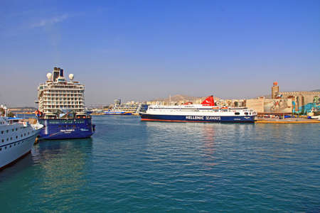 Port of Piraeus, Athens, Attica, Greece – October 18, 2018:  Port Piraeus with ferry boats and cruise ships with view of city and mountains in the background and blue sky copy space.